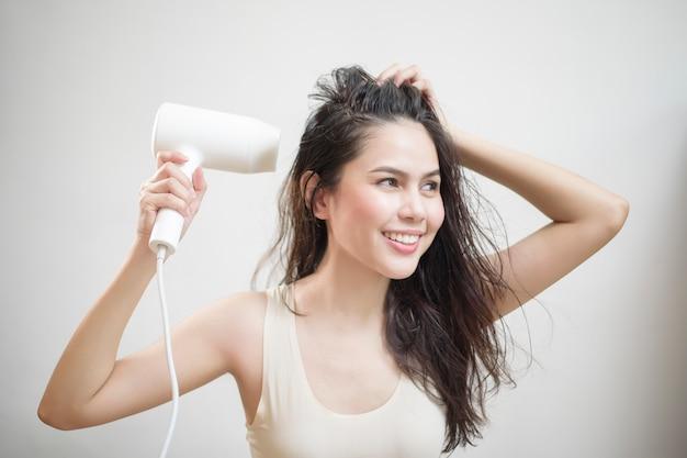 La donna si sta asciugando i capelli dopo la doccia