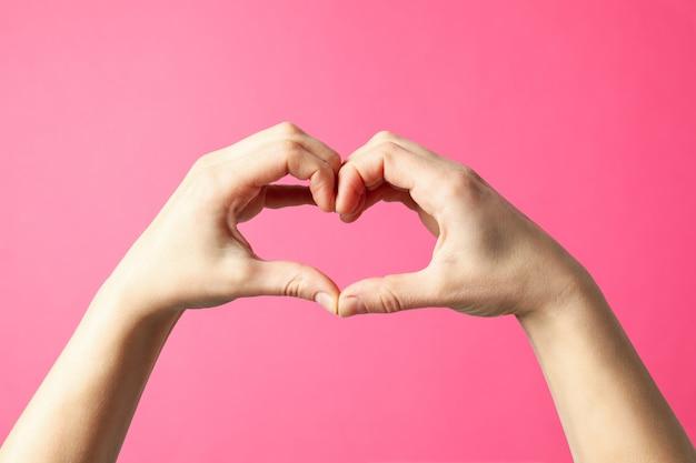 La donna si tiene per mano a forma di cuore su sfondo rosa