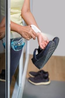 La donna si toglie le scarpe e si pulisce con l'alcool prima di entrare in una casa per proteggere