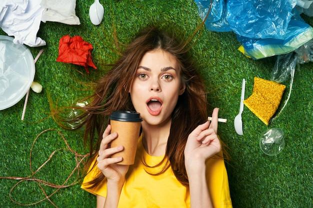 La donna si trova sull'erba inquinamento cestino dei rifiuti riciclaggio inquinamento ecologia