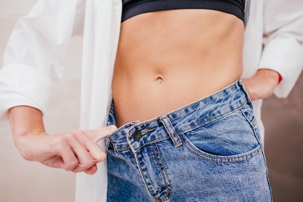 La donna snella in camicia bianca e la biancheria intima nera in jeans una taglia più grande sta mostrando una perdita di peso riuscita.