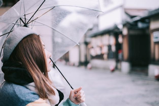 La donna sola con l'ombrello sta aspettando la pioggia sulla via nel giappone.
