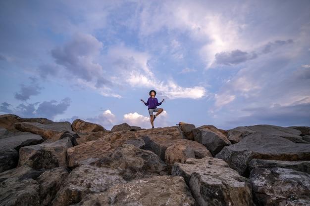 La donna sola in cappello medita sulle pietre contro un cielo blu nuvoloso, godendo della libertà, della tranquillità e della pacificazione. ricerca zen