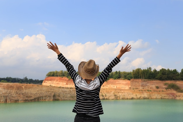 La donna solleva le sue mani su sentendosi felice e libera alla collina arancio e allo stagno verde