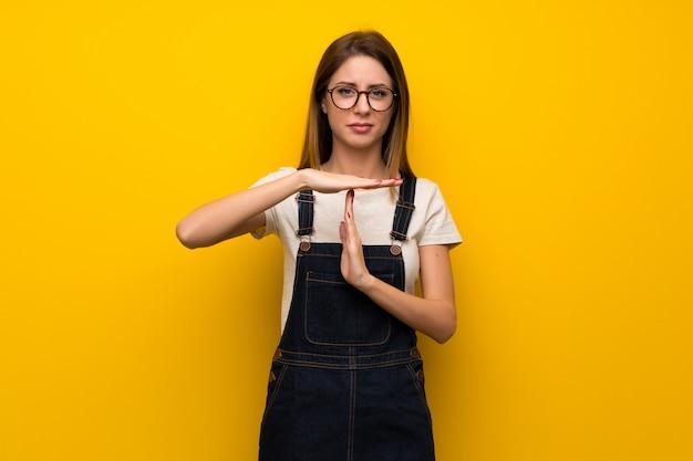 La donna sopra la parete gialla che fa il tempo fuori gesture