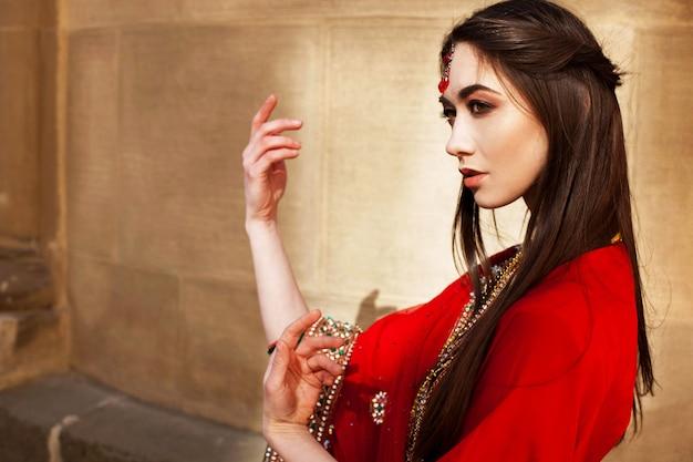 La donna sorprendente in rosso sari pone davanti al muro di pietra alle luci del mattino