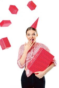 La donna sorpresa con un berretto in testa in una camicia a strisce rossa tiene un regalo in una scatola rossa con pois. i regali volano, i doni collassano