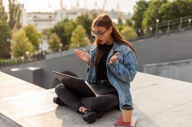 La donna sorpresa moderna dello studente in una giacca di jeans che si siede sulle scale esamina il computer portatile dello schermo. insegnamento a distanza. concetto di gioventù moderna.