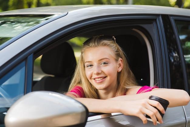 La donna sorride con la tazza di caffè in automobile