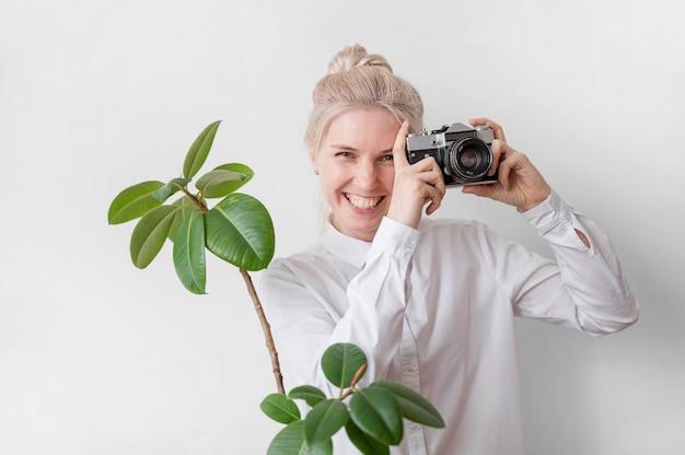 La donna sorride e tiene un concetto di arte della foto della macchina fotografica