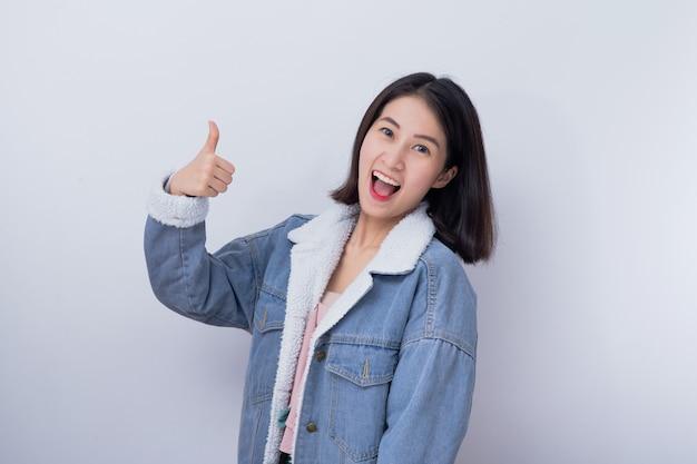 La donna sorridente caucasica che mostra la sua mano sfoglia su nel buon lavoro di concetto, giovane ragazza asiatica felice positiva che indossa il ritratto blu dell'abbigliamento casual