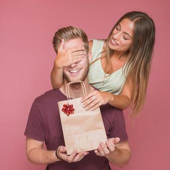 La donna sorridente che copre l'occhio del suo ragazzo gli che dà il sacchetto della spesa del regalo