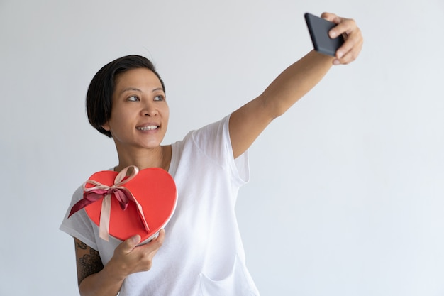 La donna sorridente che prende la foto del selfie con il cuore ha modellato il contenitore di regalo
