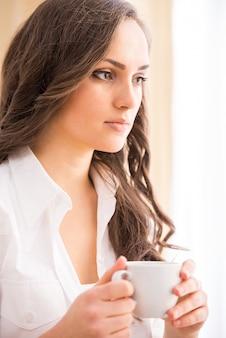 La donna sorridente con caffè sul sofà sta esaminando la macchina fotografica.