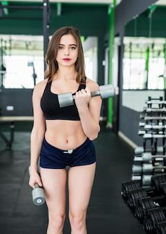 La donna sorridente con i capelli del brunette sta facendo le esercitazioni in sportclub agghindato in abiti sportivi neri