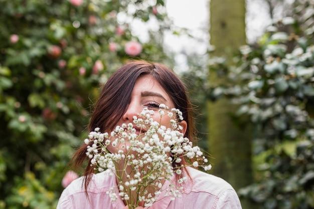 La donna sorridente con il mazzo di piante si avvicina ai fiori rosa che crescono sui cespugli