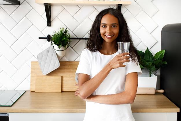 La donna sorridente del mulatto sta tenendo il vetro con acqua vicino allo scrittorio della cucina sulla cucina bianca moderna