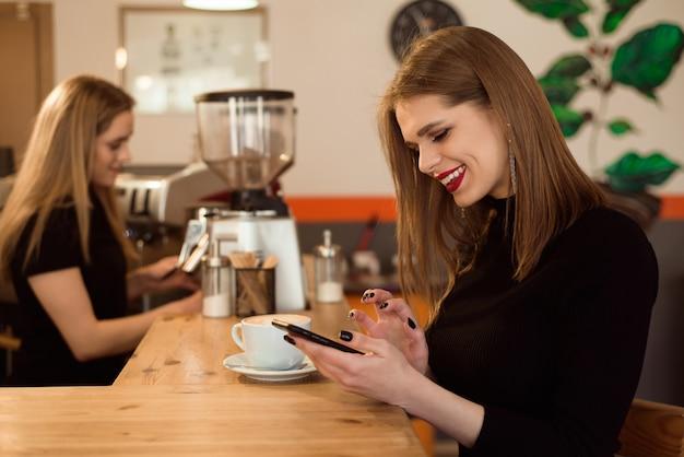 La donna sorridente di buon umore gode della tazza di caffè che si siede in un caffè.