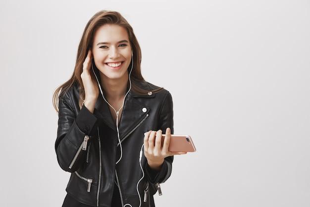 La donna sorridente di fascino che gode della musica d'ascolto in cuffie, tiene lo smartphone