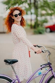 La donna sorridente di redhead in occhiali da sole e vestito, guida la bici attraverso la città durante le vacanze estive