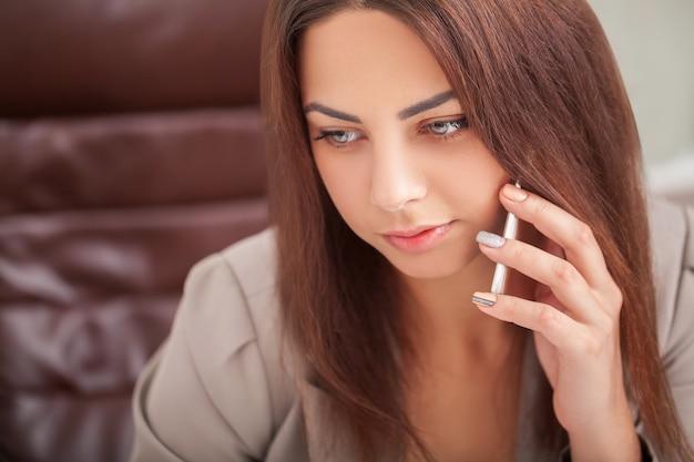 La donna sorridente in ufficio parla al telefono e utilizza il computer seduto sul grande desktop