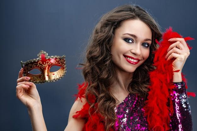 La donna sorridente in un vestito brillante tiene un boa in una mano nell'altra mano con una maschera variopinta di carnevale
