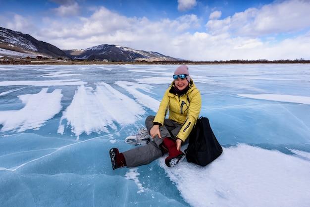La donna sorridente in una giacca gialla si siede sul ghiaccio blu del lago baikal e cambia i suoi stivali rossi in pattini da ghiaccio
