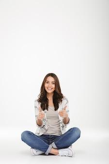 La donna sorridente integrale in jeans e scarpe da tennis che si siedono con le gambe ha attraversato sul pavimento che gesturing i pollici su, isolato sopra la parete bianca
