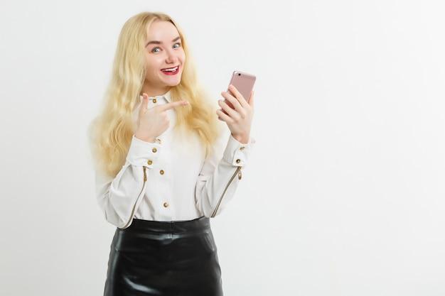 La donna sorridente sta indicando sullo smartphone che sta sul fondo bianco