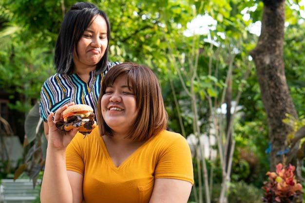La donna sovrappeso è su una sedia a rotelle e mangia un hamburger.