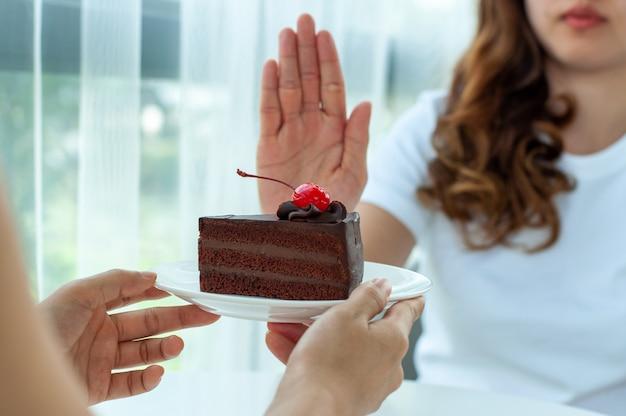 La donna spinge il piatto con una torta al cioccolato