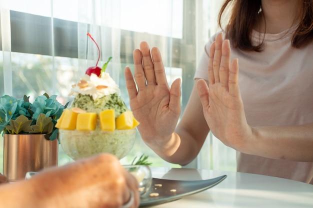 La donna spinge la tazza di bingsu si rifiuta di mangiare evitare zucchero e dolci per una buona salute. idee alimentari.