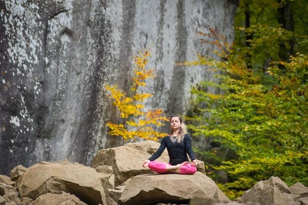 La donna sportiva adatta sta praticando lo yoga sul masso nella natura