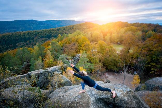 La donna sportiva adatta sta praticando lo yoga sulla cima della montagna