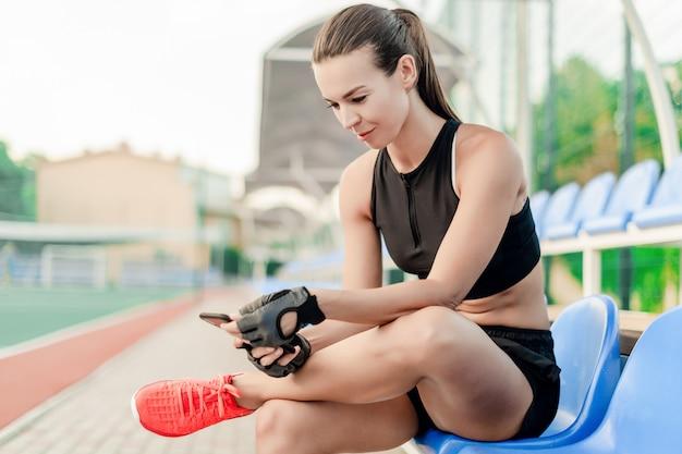 La donna sportiva adatta usa il telefono sullo stadio di mattina durante l'allenamento di forma fisica