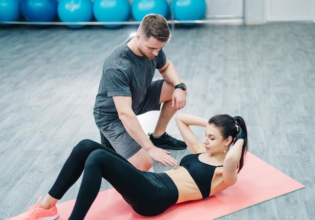La donna sportiva che fa gli addominali sul pavimento e un istruttore maschio che tiene consegnano il suo stomaco in palestra.