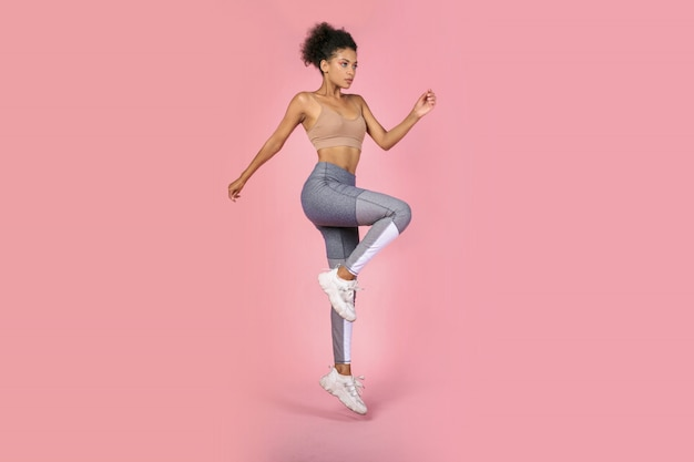 La donna sportiva che pratica lo squat si esercita in studio. donna africana in abiti sportivi che risolve su sfondo rosa.