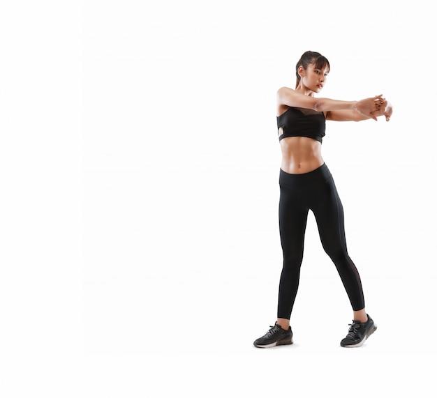 La donna sportiva ed attraente fa l'esercizio di forma fisica isolato
