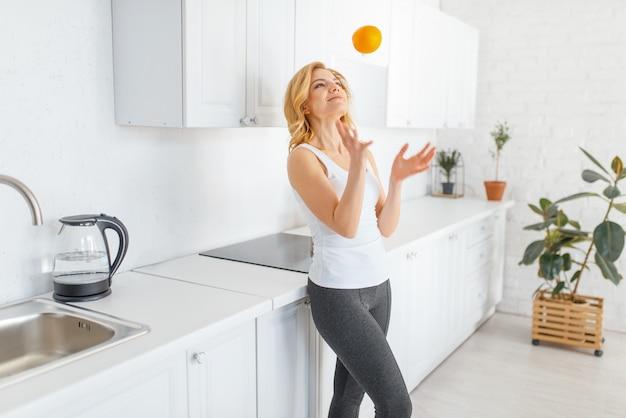 La donna sportiva lancia un'arancia, una colazione in forma in cucina.