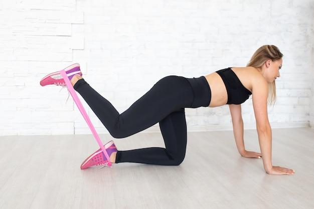 La donna sportiva usa l'elastico per lo sport