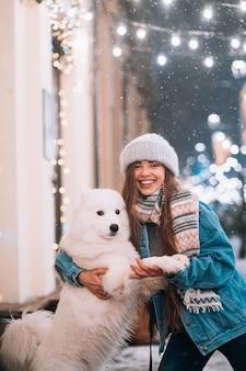 La donna sta abbracciando il suo cane in una strada di notte