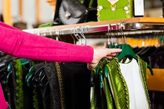 La donna sta acquistando tracht o dirndl in un negozio