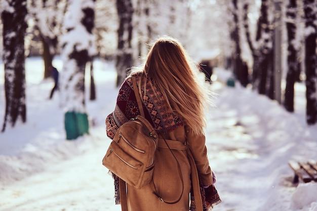 La donna sta camminando in strada in inverno