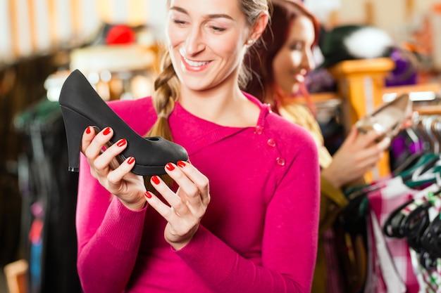 La donna sta comprando scarpe per il suo tracht o dirndl in un negozio