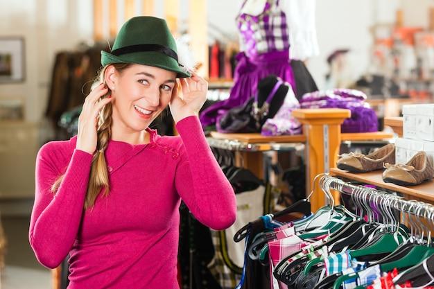 La donna sta comprando un berretto per il suo tracht o dirndl in un negozio