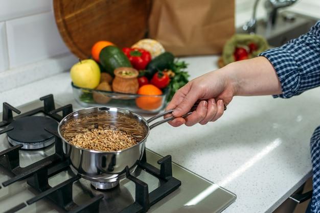 La donna sta cucinando il porridge dei grani antichi