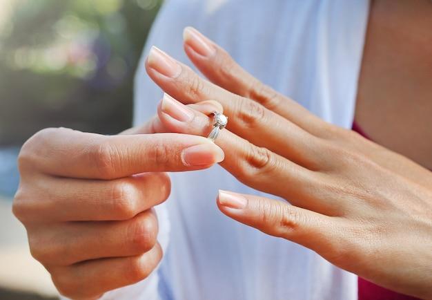 La donna sta decollando l'anello di nozze