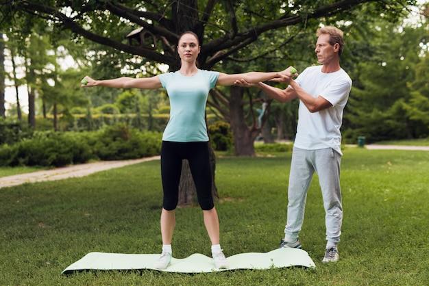 La donna sta facendo esercizi con manubri. un uomo la aiuta.