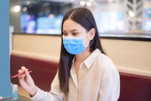 La donna sta mangiando nel ristorante con protocollo di allontanamento sociale mentre la città di blocco a causa della pandemia di coronavirus