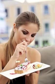 La donna sta mangiando una torta